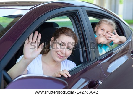 Young mother with little child waving in land vehicle. Caucasian two persons family - stock photo
