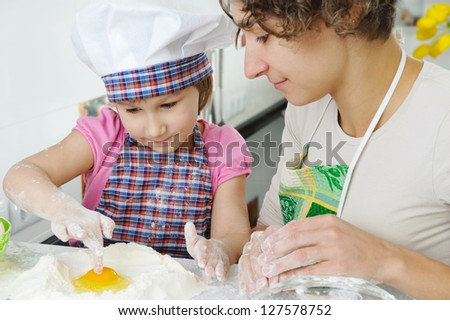 Young mother with little daughter cooking cookies - stock photo