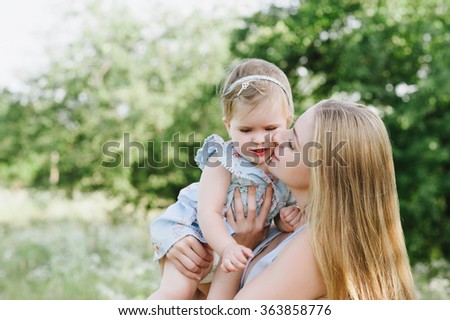 Young mother with little daughter on the nature, motherhood, tenderness, childhood, tenderness, lifestyle