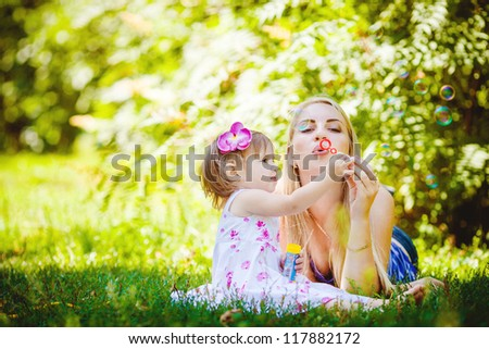 Young mother with little daughter playing in summer park outdoor - stock photo