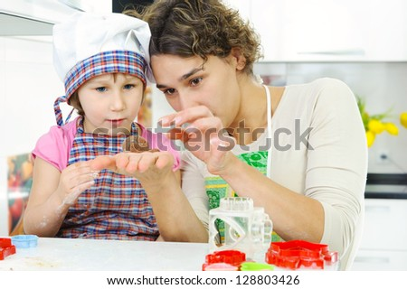 Young mother with little daughter shaping dough for cookies - stock photo