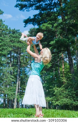 Young mother with little son at the park - stock photo