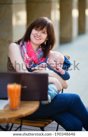 Young mother with little son working on her laptop in a cafe