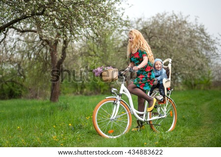 Young mother with long blonde hair in dress riding city bicycle with baby in bicycle chair, against the background of blooming fresh greenery in spring garden
