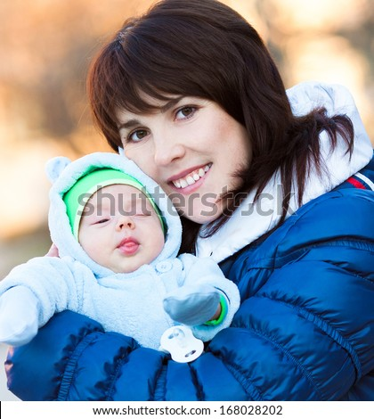 Young mother with newborn baby in winter day - stock photo