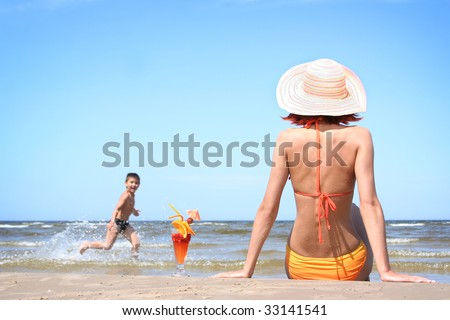 young mother with son on the beach - stock photo