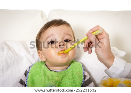 young mother with spoon and porridge feeding sweet cute little son wearing messy bib with mush stains sitting on couch eating in baby nutrition concept - stock photo
