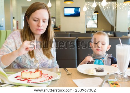 young mother with the little son sit at a table in cafe