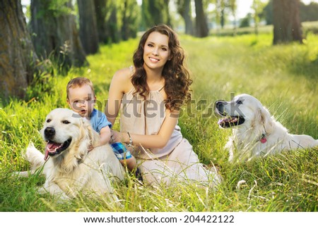 Young mother with toddler and dogs - stock photo