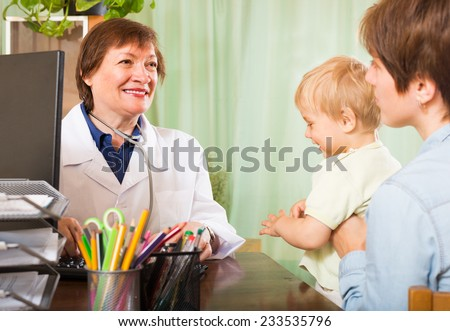 Young mother with toddler talking with smiling female pediatrician doctor at clinic - stock photo