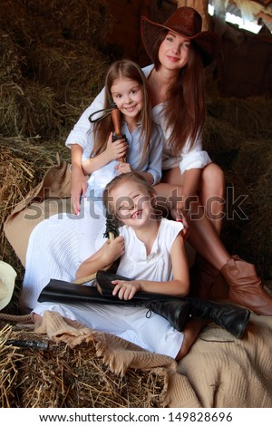 Young mother with two daughters sitting on hay ranch in the American