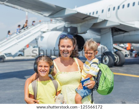 Young mother with two kids in front of airplane - stock photo