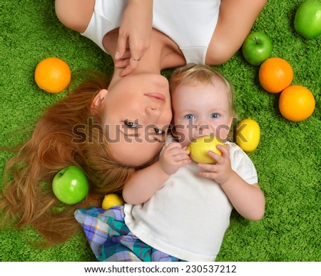 Young mother woman and daughter child baby kid girl lying down on a green grass carpet hugging smilling laughing with fruits - stock photo