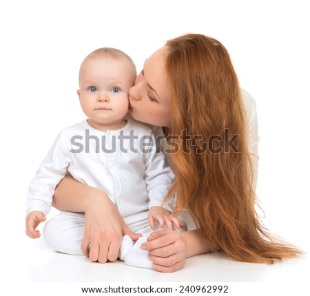 Young mother woman holding and kissing in her arms new born infant child baby kid girl in diaper on a white background - stock photo