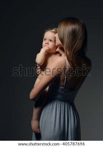 Young mother woman holding her lovely infant child baby girl in beautiful dress on dark background - stock photo