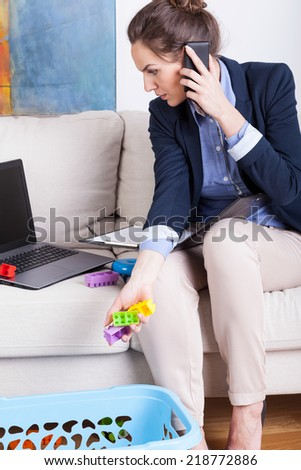 Young mother working from home and cleaning up toys - stock photo