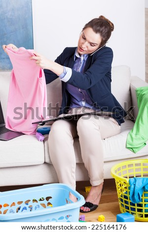 Young mother working from home and folding clothes - stock photo