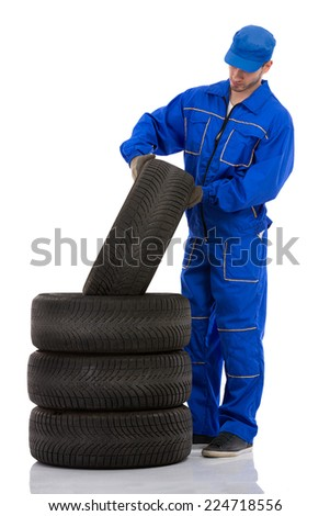 Young motor mechanic with  a tyre - stock photo
