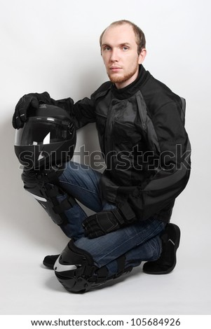 young motorcyclist man sitting and holding helmet in studio