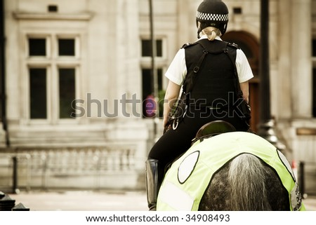 Young mounted policewoman patrolling in London - stock photo