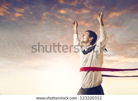 Young mulatto businessman crossing the finish line - stock photo