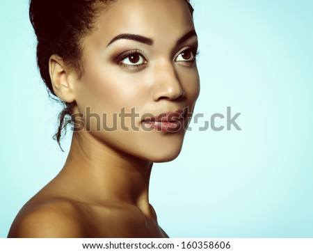 Young mulatto fresh woman with beautiful makeup, isolated on blue, toned - stock photo