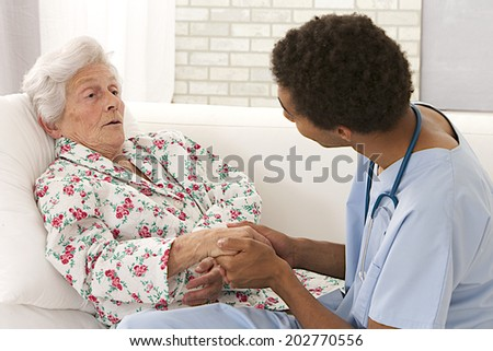Young mulatto male doctor caring about a very old female patient  - stock photo