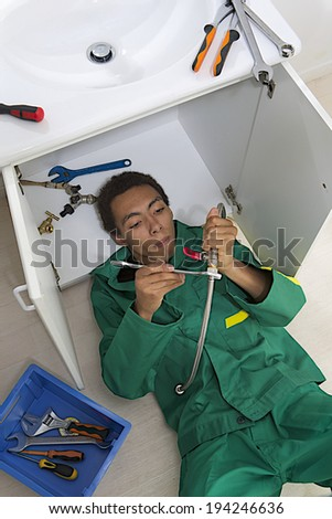 Young mulatto plumber repairing sink in kitchen.