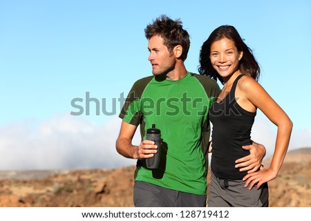 Young multicultural couple outdoors in sporty outfit. Portrait after running workout outside in mountains. Asian sport fitness woman and Caucasian man models. - stock photo