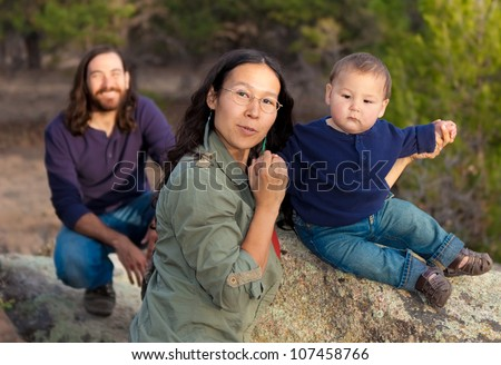 Young multicultural family in nature - shallow DOF - focus on mother & baby - stock photo