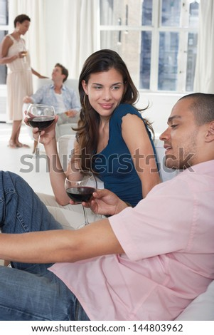 Young multiethnic couples drinking wine in living room - stock photo