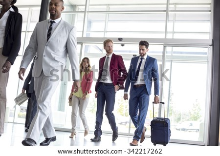 Young multiethnic international tourists arrive in airport waiting room - stock photo