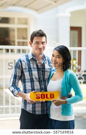 Young multiracial couple holding sold-sign - stock photo