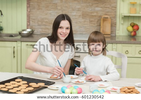 young mum and her little son baking together and decorating the cupcakes