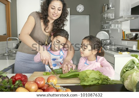 Young mum chopping vegetables with twin daughters in a family home kitchen.