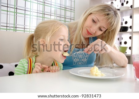 Young mum feeds the daughter with a potato in cafe