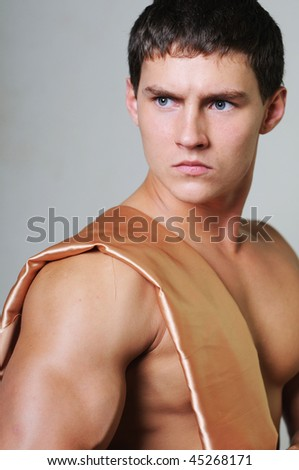 Young muscled male model with golden textile