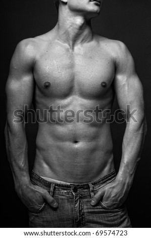 Young muscled model posing in studio - stock photo