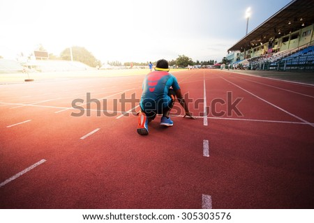 young muscular athlete is at the start of the treadmill at the stadium - stock photo