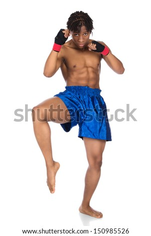 Young muscular athletic male boxer wearing blue boxing shorts and black straps for his hands. Fighter is isolated on a white background. - stock photo