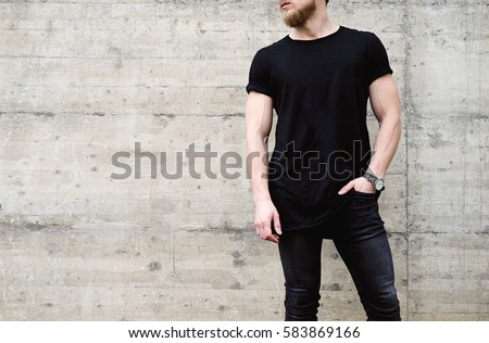 Young muscular bearded man wearing black tshirt and jeans posing in center of modern city. Empty concrete wall on the background. Hotizontal mockup