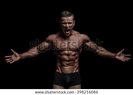 Young muscular bodybuilder posing over black background. - stock photo