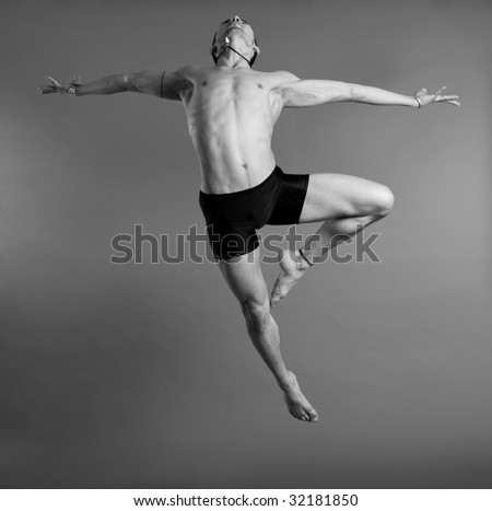 Young muscular dancer leaping over gray background - stock photo