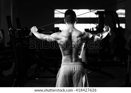 Young Muscular Fitness Bodybuilder Doing Heavy Weight Exercise For Back Or Shoulders On Machine In The Gym - stock photo