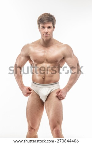 Young muscular guy in white pants posing in studio. Isolated on white