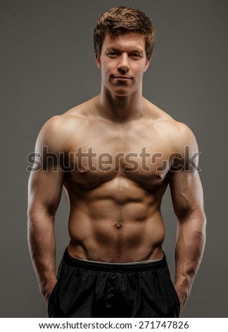 Young muscular guy posing on grey background