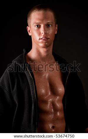 Young muscular male in hood on black background - stock photo