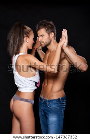 Young muscular man and a young woman touching her hands and look at each other - stock photo