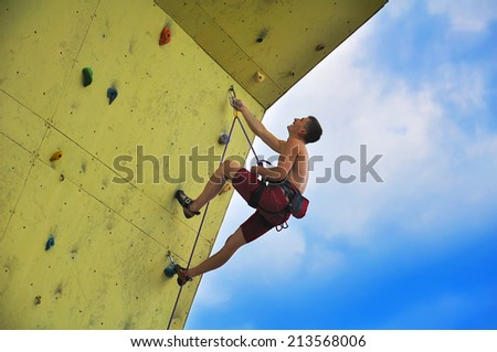 Young muscular man climbing on wall and blue sky - stock photo