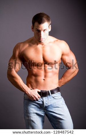 young muscular man flexing his muscles - stock photo